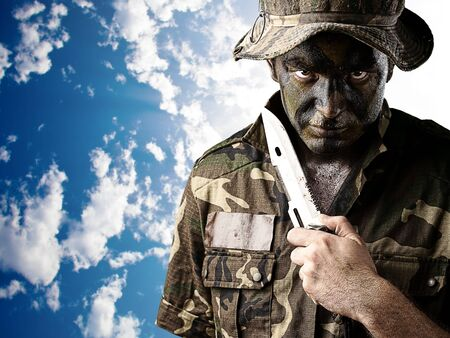 young knife: portrait of young soldier painted with jungle camouflage threating to sucide against a cloudy sky background