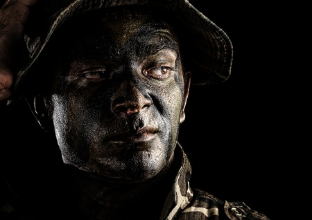 portrait of young soldier face with jungle camouflage over black background Stock Photo - 12656993