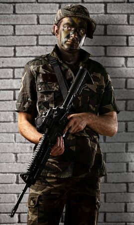 soldier with rifle: portrait of young soldier with jungle camouflage holding a rifle against a grunge bricks wall