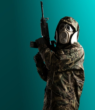 soldier with camouflage coat, rifle and gas mask over blue photo
