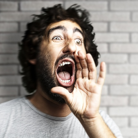 screaming head: portrait of young man shouting against a grunge bricks wall Stock Photo