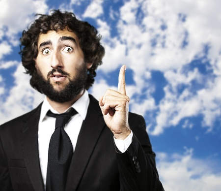 man pointing up: portrait of young business man pointing to the sky  Stock Photo