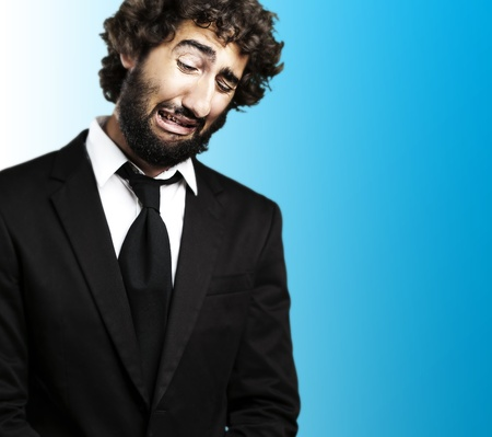 portrait of young business man with suit crying against a blue background Stock Photo - 12657004