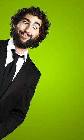 gente loca: retrato de joven hombre de negocios que muestra la lengua sobre fondo verde