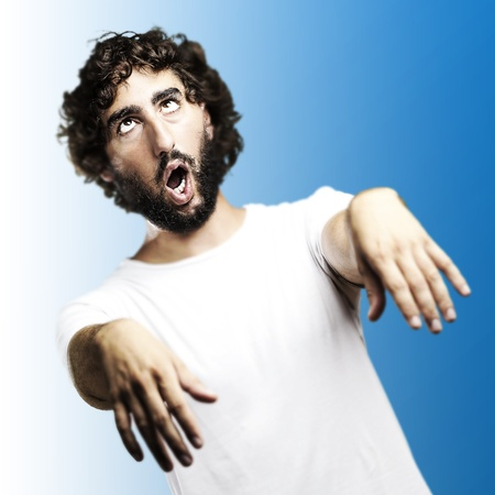 young man imitating a zombie against a blue background photo
