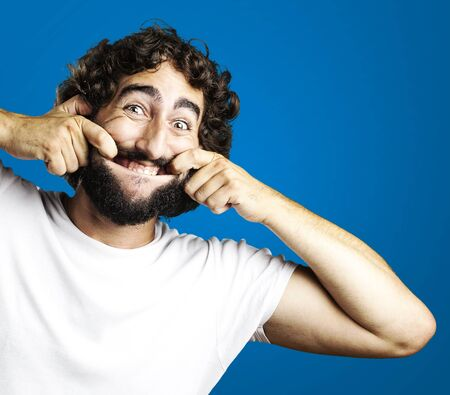 portrait of young man pulling his mouth smiling over blue background Stock Photo - 12657010