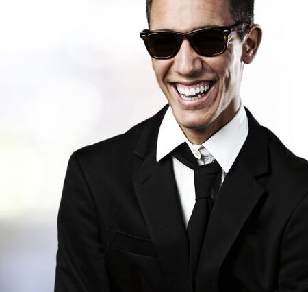 portrait of young man smiling in suit and sunglasses in a house  photo