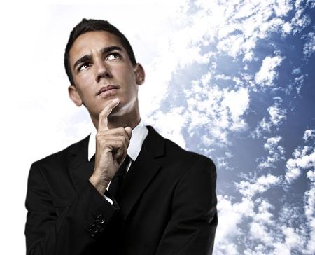 hombre pensando: retrato de pensamiento del hombre de negocios en contra de un fondo de cielo nublado