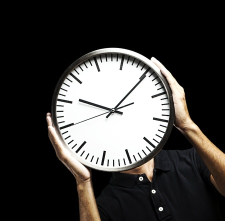 young man covering his face with a clock over black background Stock Photo - 13156215