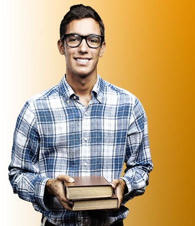 young student with glasses and shirt holding books over orange background photo