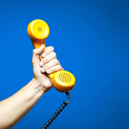 PHONE LINE: hand holding a yellow vintage telephone over blue background Stock Photo