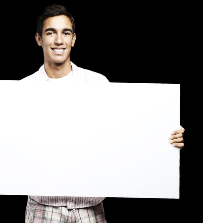 young man smiling and showing a big banner against a black background photo