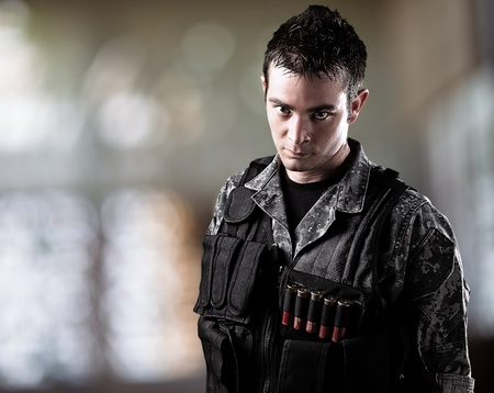 gun room: portrait of serious young soldier wearing urban camouflage indoor Stock Photo