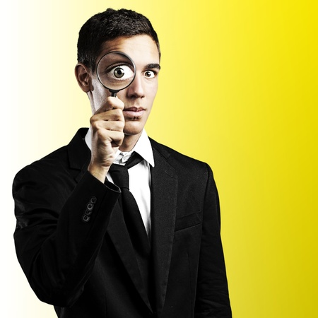 spy glass: portrait of young man with magnifying glass on a yellow background Stock Photo