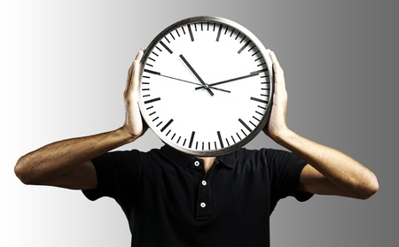 young man holding big clock covering his face over grey photo