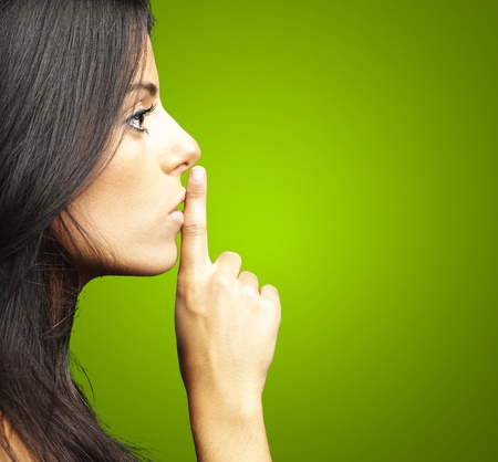 portrait of young woman doing silence sign against a green background
