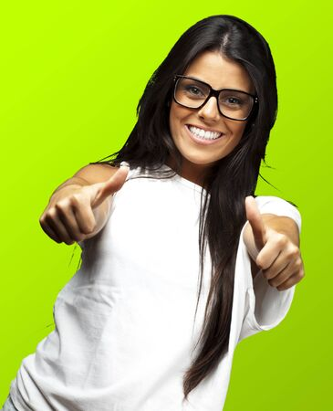 portrait of a pretty young woman doing good symbol against a green background photo