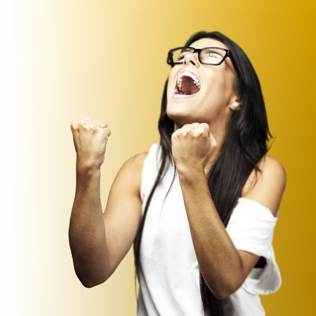 portrait of young winner woman with glasses over a yellow background Stock Photo - 12657082