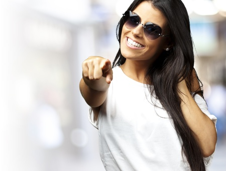 1 and crowd: portrait of young woman wearing heart sungalasses pointing at a crowded place Stock Photo