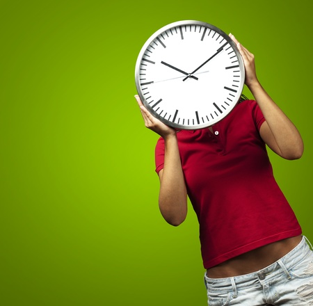 woman holding clock in front of head against a green background photo