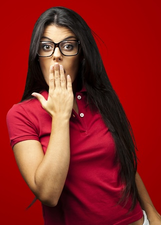 portrait of young woman covering her mouth with hand against a red background photo