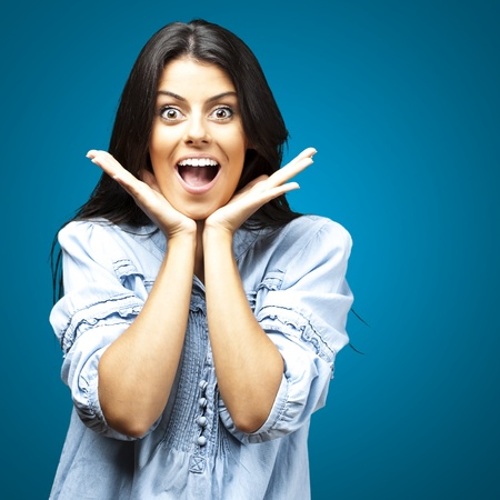 Surprise: portrait of surprised young woman against a blue background