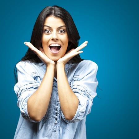 cara sorprendida: retrato de joven mujer sorprendida sobre un fondo azul