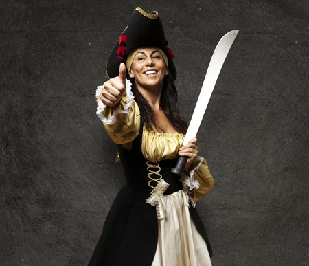 portrait of pirate woman holding a sword and gesturing ok against a grunge background photo