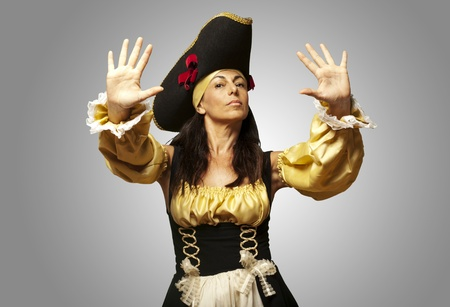 portrait of pirate woman gesturing stop against a grey background photo