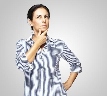 donna pensiero: Ritratto di middle aged woman pensando su sfondo grigio