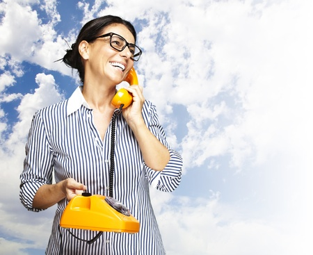 portrait of a middle aged woman talking on vintage telephone against a cloudy sky photo
