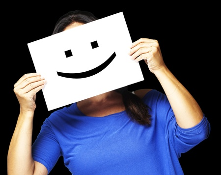 Woman showing a happy emoticon in front of face against a black background photo