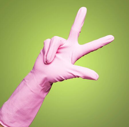 pink gloves of maid gesturing number three against a green background Stock Photo - 12377891