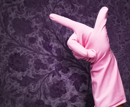 housewife gloves: pink rubber gloves pointing against a vintage background