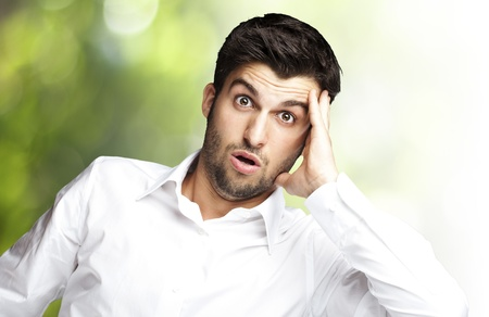 scared man: portrait of young man surprised against a nature background Stock Photo