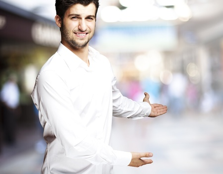 inviting: portrait of a handsome young man gesturing welcome at a crowded place Stock Photo