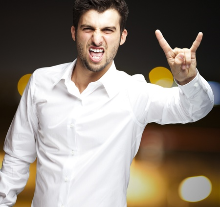 young man doing a rock gesture against a city by night photo