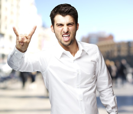 young man doing a rock gesture against a street background photo