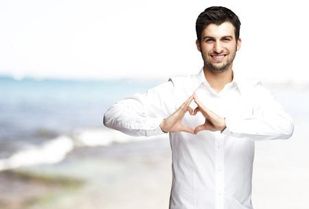 Retrato de hombre joven que hace gesto de corazón contra un mar de fondo