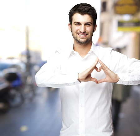 sweet heart: young man doing a heart gesture against a street background
