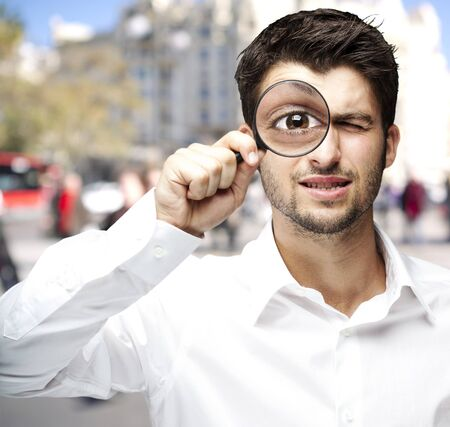 loupe: young man holding a magnifying glass against a street background Stock Photo
