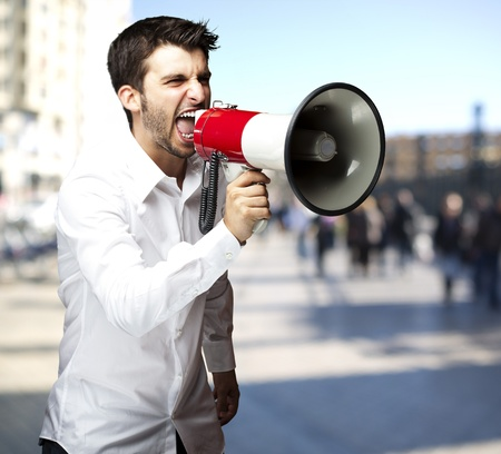 young man shouting through a megaphone against a street background