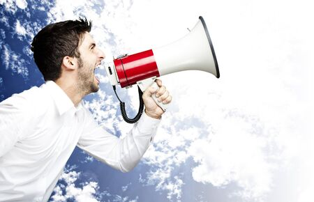 portrait of young man handsome shouting using megaphone against a blue sky background Stock Photo - 12656273