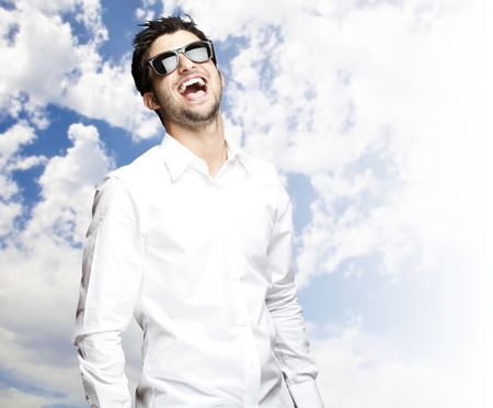 portrait of a handsome young man wearing sunglasses and enjoying against a cloudy sky background photo