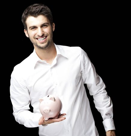portrait of young man smiling and holding a piggy bank against a black background Stock Photo - 12656171