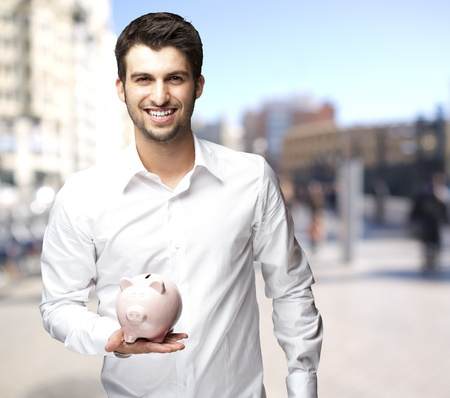handsome man holding a piggybank against a street background photo