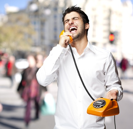 young man laughing while talking on a vintage telephone against a street background photo