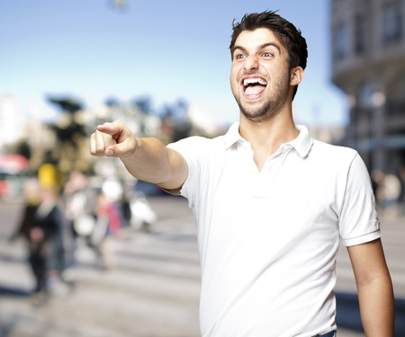 young man laughing and pointing against a street background photo