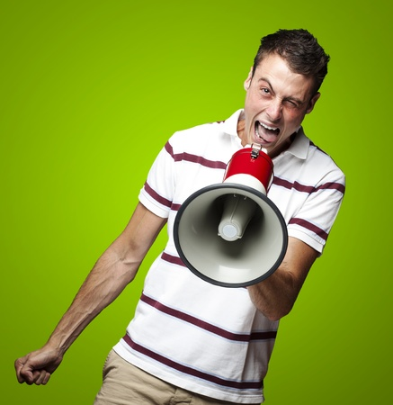 portrait of young man shouting with megaphone against a green background photo