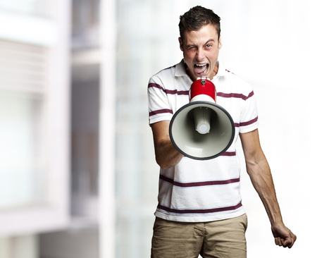 portrait of young man shouting with megaphone against a city background photo
